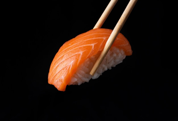 Traditional japanese nigiri sushi with salmon placed between chopsticks