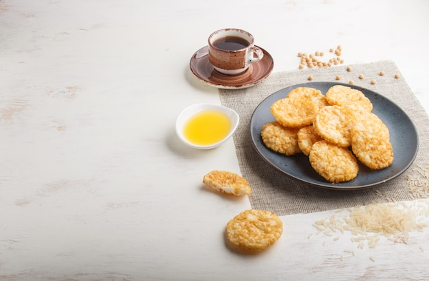 Traditional japanese rice chips cookies with honey and soy sauce on a blue ceramic plate and a cup of coffee on a white wooden background. side view.