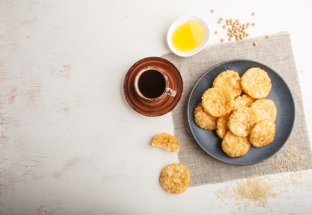 Traditional japanese rice chips cookies with honey and soy sauce on a blue ceramic plate and a cup of coffee