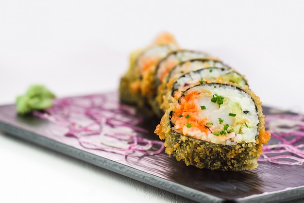 Traditional japanese rolls and sushi on a black stone plate