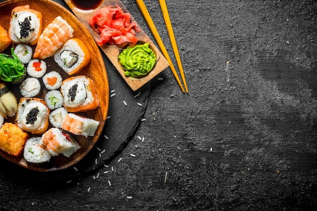 Traditional japanese rolls and sushi in a plate on a stone board. on black rustic background