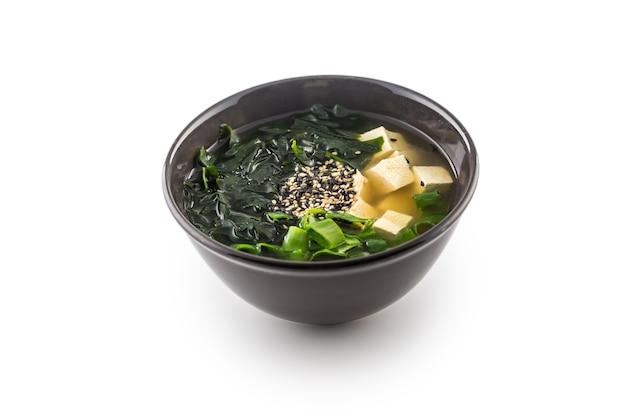 Традиционный японский суп мисо с водорослями тофу и молодым луком, изолированным на белом.
