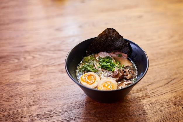 伝統的な日本のスープラーメン、麺、鶏肉のスライス、卵。閉じる。