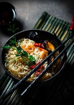 어두운 배경에 새우, 아시아 국수, 홍합 칠리 고추를 넣은 전통적인 일본 수프 라면. 아시아 스타일의 음식. 텍스트를 위한 공간입니다. 해산물과 마이크로 그린을 곁들인 국수