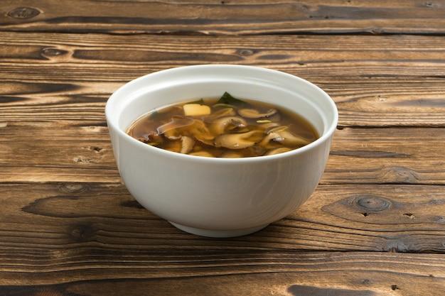 木製の台所のテーブルの上の白いセラミックボウルに椎茸、玉ねぎ、豆腐チーズを入れた伝統的な日本のスープ。