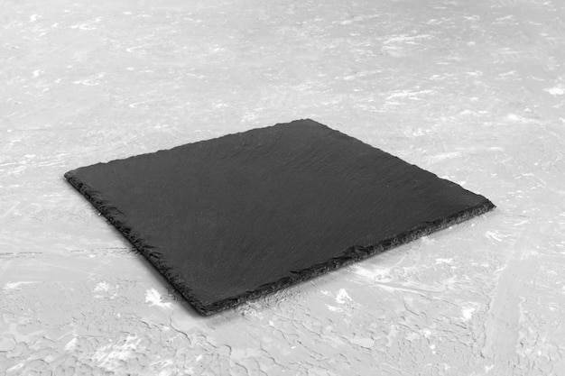 Traditional japanese square empty black slate plate on grey textured
