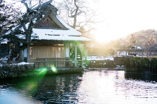 Traditional japanese style house at oshino hakkai with mt.fuji with flare light. landmark of life japan's strong community have clear pool, famous tourist destination village in japan