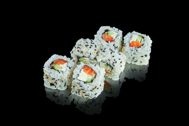 Traditional japanese sushi roll with with salmon, sesame seeds and cream cheese on a black surface with reflection. close up. food photo for menu