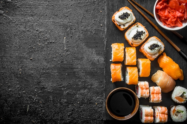 Traditional japanese sushi rolls with ginger and soy sauce on a black stone board. on black rustic surface