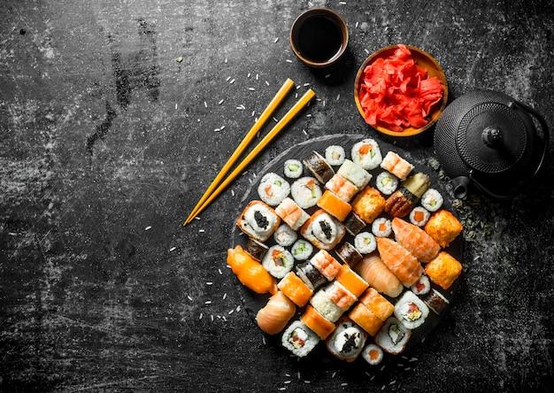 Традиционные японские суши-роллы с соевым соусом и маринованным имбирем. на темном деревенском фоне
