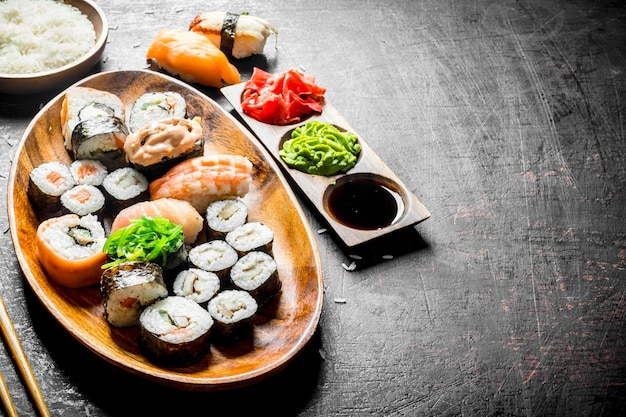 Traditional japanese sushi and rolls with soy sauce and ginger. on dark rustic surface