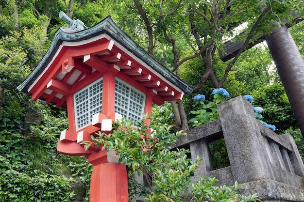 後ろに石の門の破片がある緑の森の伝統的な日本の木製ランタン