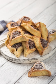 말린 살구, 날짜와 함께 전통적인 유대인 hamantaschen 쿠키. 푸림 축하 개념입니다. 카니발 휴일 배경입니다. 선택적 초점. 공간을 복사하십시오.
