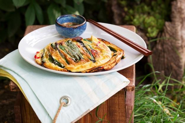 파와 칠리를 곁들인 전통 한국 튀김에 간장을 곁들인 요리.