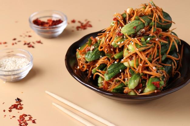 伝統的な韓国のキムチのおやつ。にんじん、ねぎ、にんにく、ごま、発酵野菜、明るい背景を詰めたキュウリ