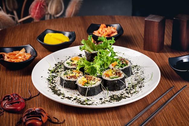 한국 전통 롤 김밥. 쇠고기와 함께 스시 롤. 고기. 한국 전통 요리 세트 레스토랑 음식 배경입니다. kimbap 나무 배경에 김치를 곁들여.