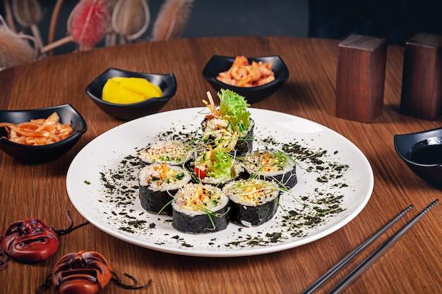 한국 전통 롤 김밥. 참치 롤. 고기. 한국 전통 요리 세트 레스토랑 음식 배경입니다. kimbap 나무 배경에 김치를 곁들여. 해물. 건강에 좋은 음식 생선