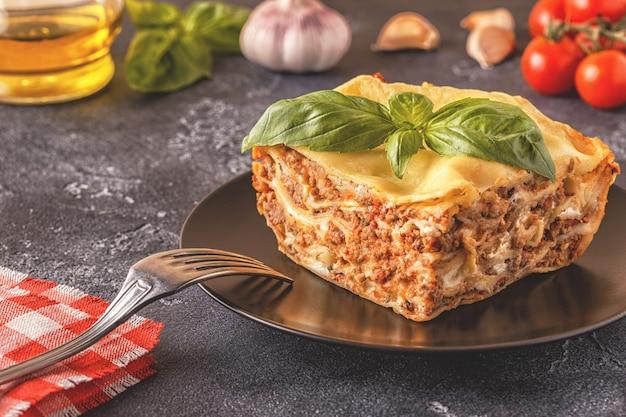 Традиционная лазанья с соусом болоньезе из говяжьего фарша и соусом бешамель, покрытая листьями базилика.