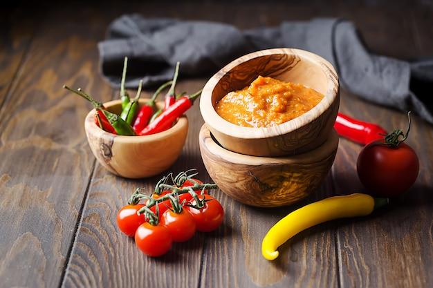 木製のボウルに伝統的なラテンアメリカのメキシコのサルサソースと暗いテーブルの食材。