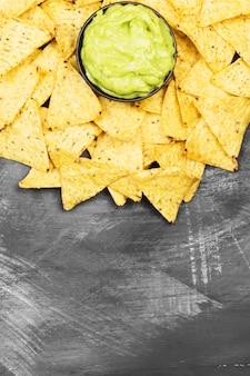 Традиционный латиноамериканский соус гуакамоле в миску и начос на темном фоне. вид сверху, скопируйте пространство. пищевой фон