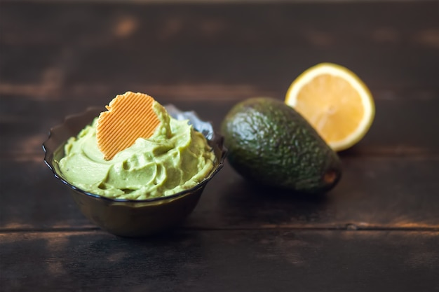 Traditional latinamerican mexican sauce guacamole in bowl with cracker, avocado and lemon on dark background.