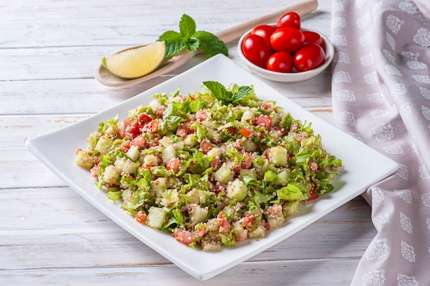 Traditional lebanese salad tabouli tabule with wheat, herbs, tomatoes, mint and lemon.