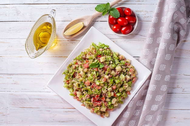 Traditional lebanese salad tabouli. with wheat, herbs, tomatoes, mint and lemon.