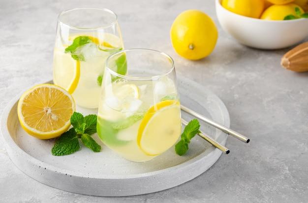 Традиционный лимонад с лимонной мятой и льдом в стакане с металлической соломкой на бетонном фоне