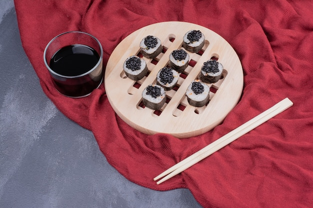 Traditional maki sushi roll with chopsticks and soy sauce on red tablecloth.