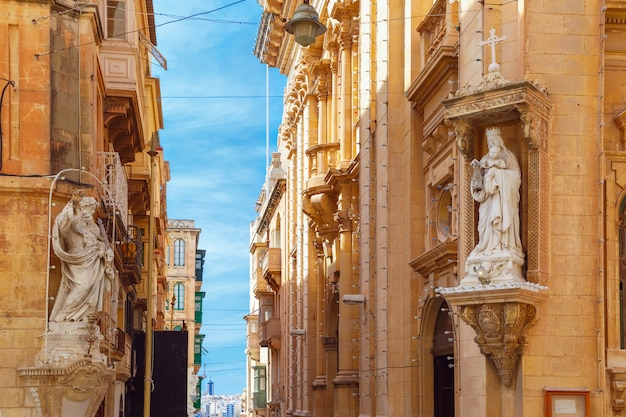 The traditional maltese street stairs with corners of houses, decorated with statues of saint and our lady in valletta, capital city of malta