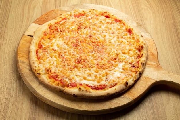소박한 나무 배경에 전통적인 마르게리타 피자입니다.