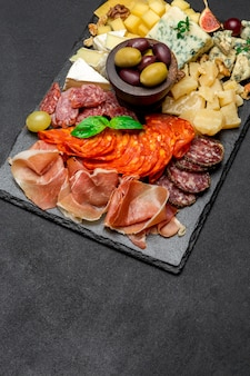 Traditional meat and cheese plate - parmesan, meat, sausage and olives