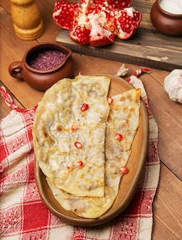 Traditional meat vegetable gutab, qutab, gozleme on wooden board with sumakh and pomegranate seeds