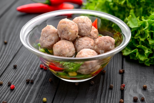 Traditional meatballs with chicken meat with chicken broth, on a black surface