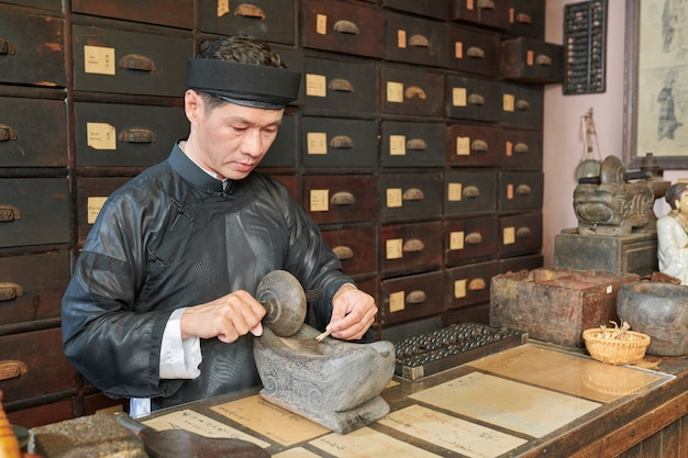 Traditional medicine practitioner milling treatment ingredients