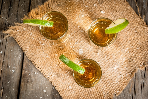 Traditional mexican alcoholic beverage is a golden tequila in tall glasses with a slice of lime and salt on the background on a wooden rustic table