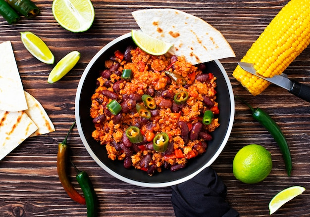 Traditional mexican chili con carne served on a rustic wooden table in a pan with corn, mexican tortilla bread, lime and jalapeño. top view.