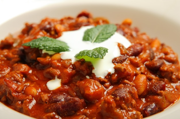 Traditional mexican chilli beans soup served in a white bowl over wooden background