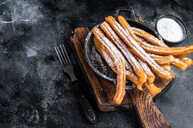 Traditional mexican dessert churros with sugar powder in a pan. black