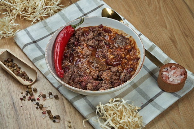 A traditional mexican dish is chili con carne soup with stewed beef in a composition with spices on a wooden table. tasty food photography