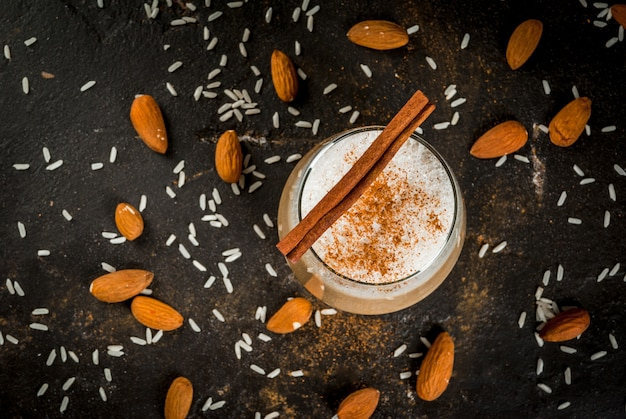 Traditional mexican drink horchata latte - coffee mixed with horchata a cocktail of almonds rice vanilla and cinnamon on a black concrete table