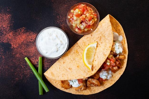 닭고기와 야채를 곁들인 전통적인 멕시코 파 히타는 흰색과 붉은 소스, 레몬, 신선한 파를 곁들인 옥수수로 제공됩니다. 평면도. 어두운 배경. 공간 복사
