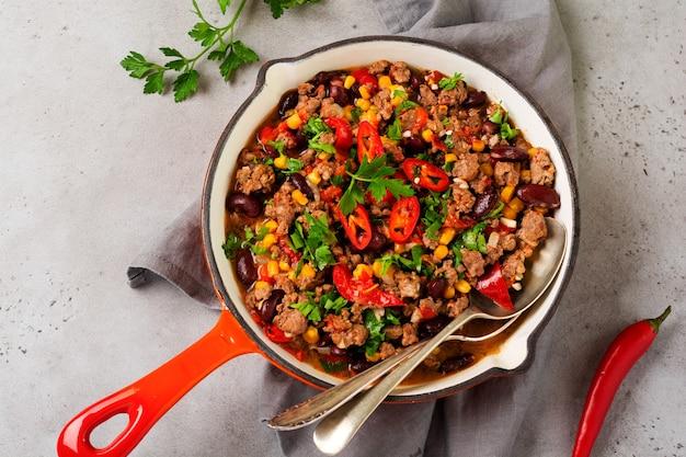 Традиционная мексиканская еда - чили кон карне с мясным фаршем и тушеным овощем в томатном соусе в чугунной сковороде на светло-сером фоне из сланца или бетона. вид сверху с копией пространства