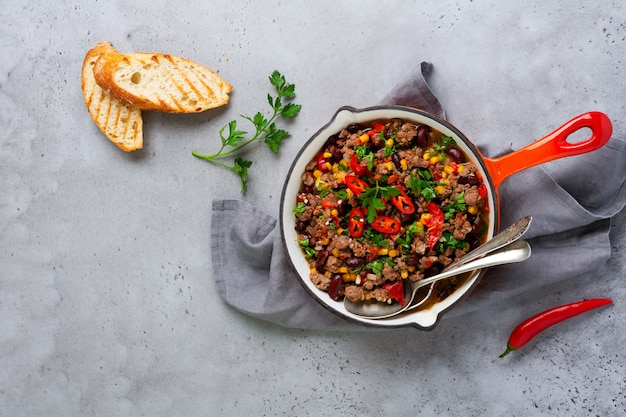 Traditional mexican food - chili con carne with minced meat and vegetables stew in tomato sauce in a cast iron pan on light gray slate or concrete background. top view with copy space