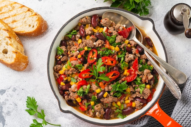 Traditional mexican food - chili con carne with minced meat and vegetables stew in tomato sauce in a cast iron pan on light gray slate or concrete table. top view with copy space.