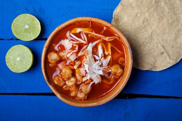 Традиционный мексиканский суп из красного позоле с тостадой и лаймом на синем фоне