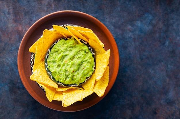 점토 그릇에 토르티야 칩을 넣은 전통 멕시코 소스 과카몰리. 어두운 배경에 나초 칩을 넣은 아보카도 한 그릇. 공간을 복사합니다. 평면도