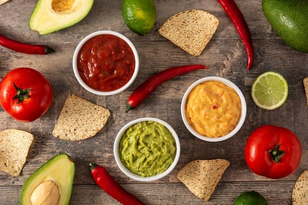 伝統的なメキシコのソース。木製のテーブルにワカモレ、チリペッパーソース、チーズソース