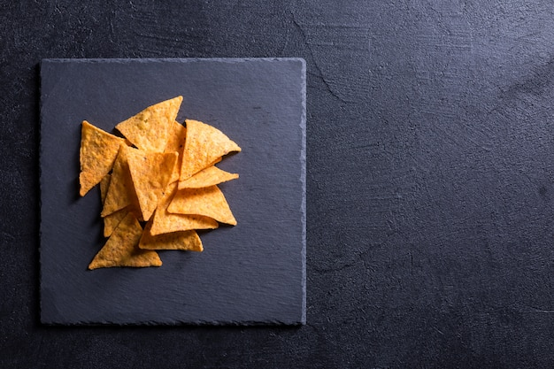 Традиционные мексиканские закуски начос на черном фоне