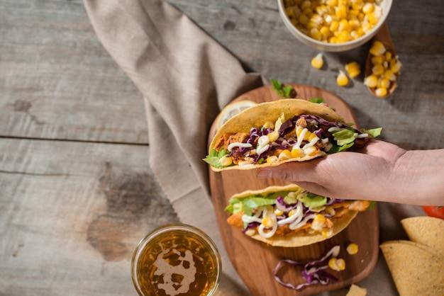 木製のテーブルに鶏肉と野菜を添えた伝統的なメキシコのタコス。ラテンアメリカ料理。